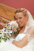 Wedding. Portrait of bride with bouquet in hands indoors.
