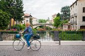 picture of vicenza  - Saint Paul bridge in Vicenza with a girl riding a bike and a view of Saint Michele bridge in the background - JPG