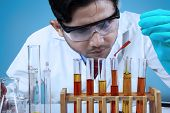 stock photo of combine  - Asian scientist combining the chemical fluid using a pipette into test tube - JPG