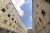 image of prison uniform  - Prison walls surrounds walking yard in prison - JPG
