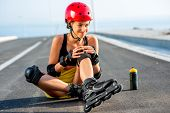 pic of sports injury  - Young sport woman with rollers in yellow skirt and red helmet having knee injury sitting on the highway - JPG