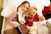 picture of cute bears  - Portrait of cute smiling girl reading book with teddy bear in bed - JPG