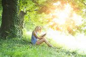 pic of natural blonde  - Pretty alluring blond woman sitting outdoor with book in summer on green natural background horizontal picture - JPG