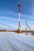 image of antenna  - Cellular antenna red and white in the winter against the blue sky - JPG