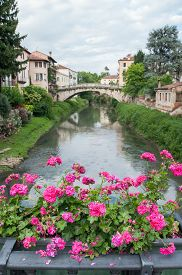 stock photo of vicenza  - Flowered iron balcony of Saint Paul bridge in Vicenza with a view of Retrone river and Saint Michele bridge in the background - JPG