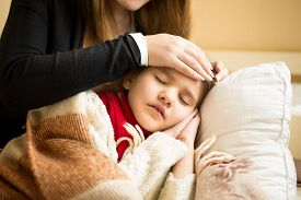 pic of forehead  - Closeup photo of caring mother holding head on sick daughter forehead - JPG