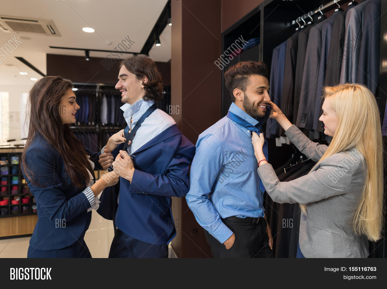 handsome business man trying suit clothes w assistant help handsome business man trying suit clothes w assistant help knotting the necktie fashion shop customers