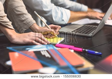 Following this method. Close up of female student hands writing in notebook with her friend working with laptop in background