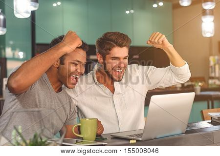 This is our victory. Shot of two male friends celebrating and looking at laptop while spending time in cafe