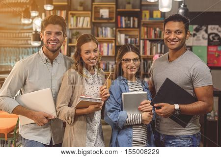 Working together to prepare for finals. Group of young people studying together for upcoming exams while standing at library