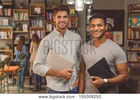 Enjoying university life. Shot of two male college students studying together at library and looking at camera smiling