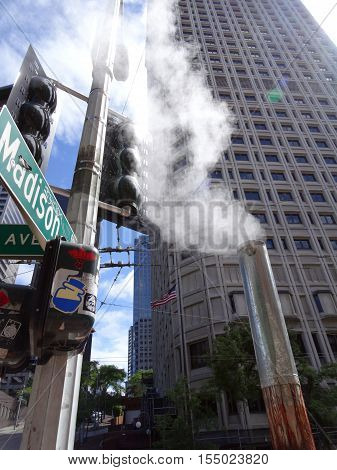 SEATTLE - JUNE 24: Steam flows out of pipe on Madison street in Downtown Seattle. The Seattle Steam Company is a district heating public utility that provides steam (generated by burning natural gas diesel oil and recycled wood) to over 175 business in do