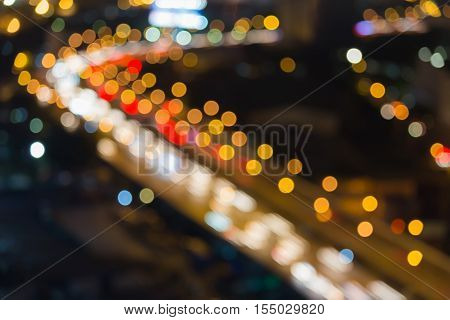 Night blurred lights city highway interchanged with office building background