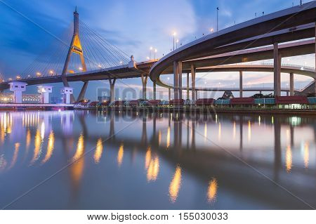 Suspension bridge connect to highway overpass interchanged river front with twilight sky background