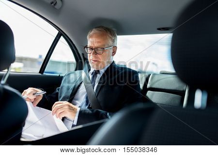 transport, business trip, paperwork and people concept - senior businessman with documents and pen driving on car back seat