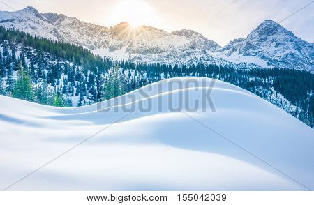 Snowy mountains and piles of snow - Winter scenery with the Austrian Alps in the background and a big pile of snow in the foreground. Image taken in Ehrwald municipality Austria.