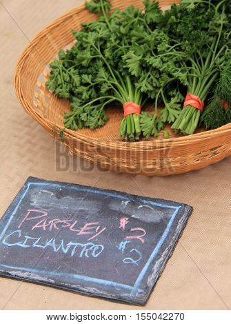 Wood basket with parsley and cilantro, set in back of a chalkboard  sign that says the same.