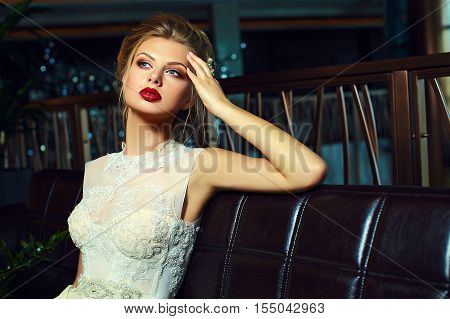 High fashion look.glamor closeup portrait of beautiful sexy stylish blond bride young woman model with bright makeup with red lips with perfect clean skin in wedding dress