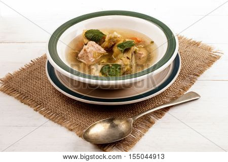 fish soup with vegetables and parsley in a bowl