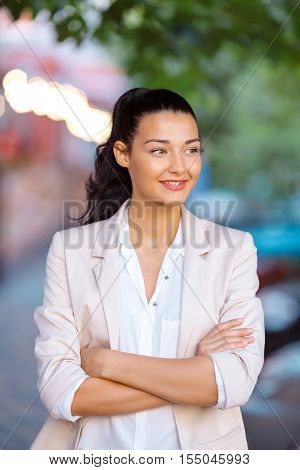 Beautiful brunette business woman standing outdoors against city space background with her arms crossed and looking away. Copy space
