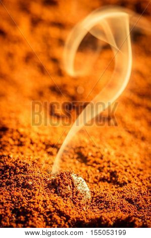 Smell of roasted ground coffee on brown background