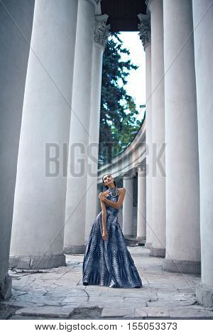 young lady in dark dress at the entrance of neoclassical building