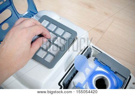 Hand replacing the air filter in a modern vacuum cleaner
