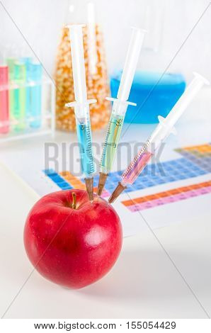 Three Syringes In Red Apple. Genetically Modified Food Concept.