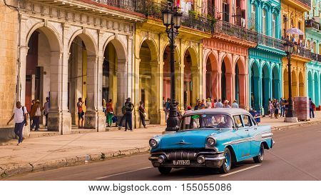 Havana Cuba on December 22 2015: A blue oldtimer taxi is driving through Habana Vieja in front of a colorful facade