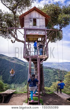 Banos Ecuador on November 18 2015: Tourists enjoying the giant swing at the treehouse Casa del Arbol in the Andes near Banos Ecuador. The view from the swing is breathtaking.