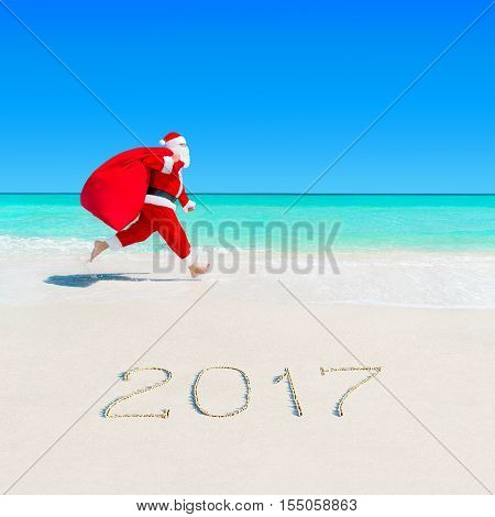 Christmas Santa Claus running on the jump at tropical ocean white sandy beach with large red sack full of gifts and surprises season 2017 New Year vacation and travel agencies price discounts concept