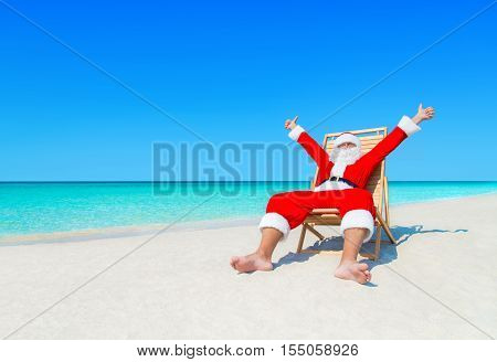 Happy Christmas Santa Claus on beach chair at ocean tropical beach sand thumbs up positive gesturing - New Year's holidays travel destinations concept