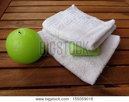 Set bath: Terry white towels, green soap and a round candle. All this on wooden boards