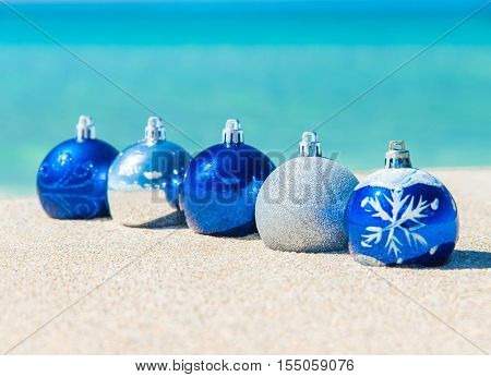 Christmas tree balls decorations on the sand of tropical ocean beach - winter New Year's holidays in hot countries concept