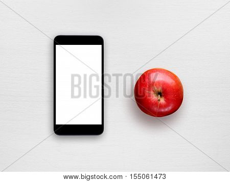 Smartphone with blank screen and red apple on white table top view