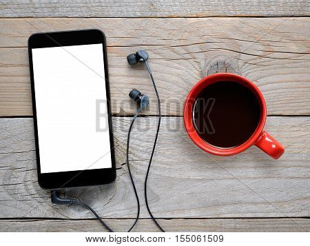 Smartphone with headphones and coffee cup on wooden table top view