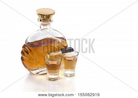 Bottle with shot glasses tequila and chocolate on white background