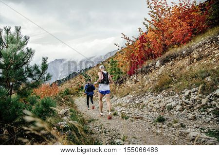 two runners marathon run mountain marathon. autumn landscape of trees with red-yellow leaves