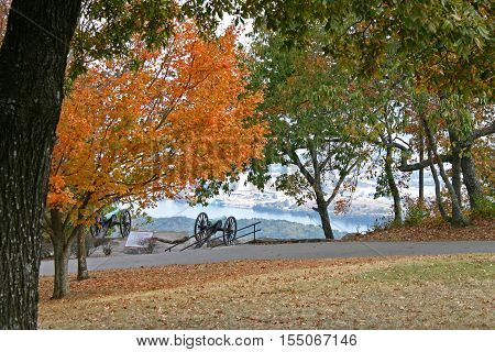a pair of Civil War cannons overlook Chattanooga, Tennessee, from Lookout Mountain, amid autumn foliage