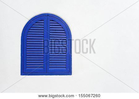 Blue wooden window closed with wooden shutters on white stucco wall with copy space