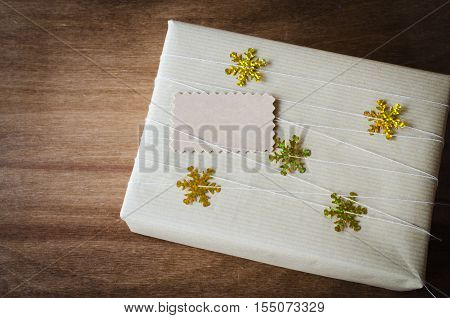 Christmas Kraft Gift Box in Rustic Style with Decorativ Snowflakes and Blank Gift Tag on Wooden Background. View from above with copy space.