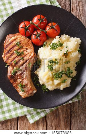 Grilled Pork T-bone Steak Garnished With Mashed Potatoes Close-up. Vertical Top View