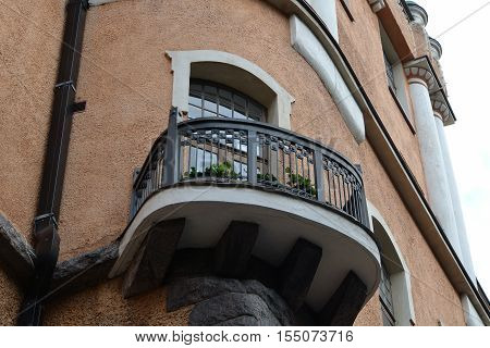 Brown plastered walls of the house with black iron railing balcony