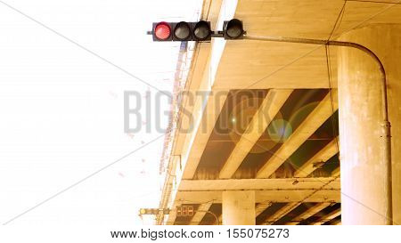 Traffic red lighting stop symbol under the concrete bridge have filter lens flare and left is sky white color for word.
