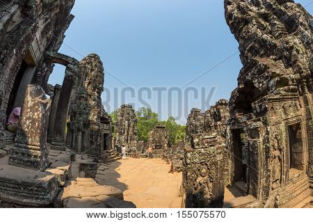 ANGKOR WAT CAMBODIA - JANUARY 27 2015: Unidentified tourists at Bayon temple in Angkor Wat. Angkor Wat is the largest Hindu temple complex and religious monument in the world
