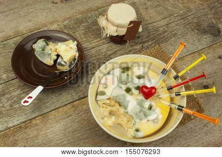 Moldy pudding and syringe. Treatment of the disease. Mold and antibiotics. Poisonous food full of mold. Unhealthy food. Spores of the fungus for food. Growing mold.
