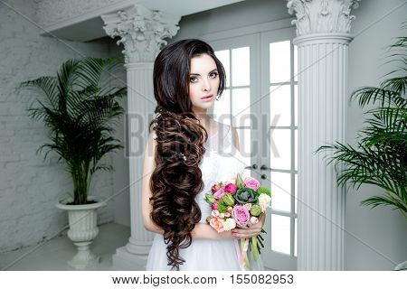 Fashion Beauty Model Girl with Flowers Hair. Bride. Perfect Creative Make up and Long Wavy Hair. Hairstyle. Beautiful Woman with Shiny Brown Hair. Bouquet of Beautiful Flowers.