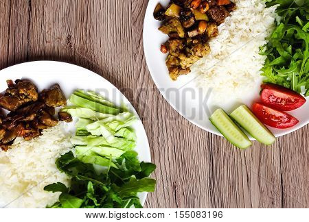 Top View Of Two Plates With Healthy Lunch. White Rice, Thai Fried Meat And Vegetables. Flat Lay On W