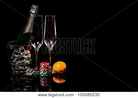Bottle of champagne in an ice bucket with two wineglasses and colorful chips with mandarin
