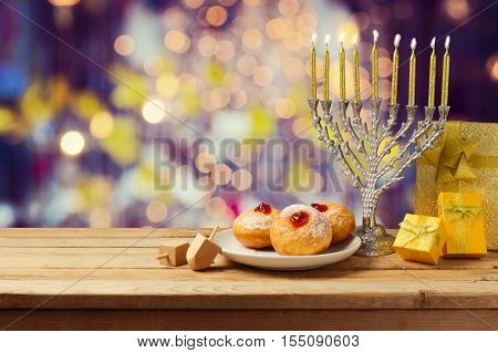 Hanukkah holiday sufganiyot and menorah on wooden table over night bokeh background
